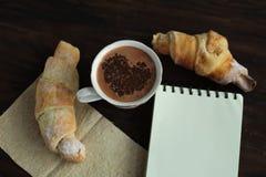 浪漫早餐-可口新鲜的新月形面包,可可粉 图库摄影