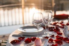 浪漫晚餐设定,与玫瑰花瓣的红色装饰在餐馆 免版税图库摄影