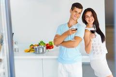 浪漫晚餐 夫妇饮用的酒在厨房里 年轻peop 免版税库存照片