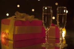 浪漫构成两觚香槟和礼物在弄脏 免版税库存照片
