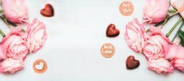浪漫桃红色玫瑰与字法的束用在心脏形状的巧克力和卡片充满对您的爱白色木背景的, 免版税库存图片
