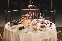 浪漫桌设置用酒,在箱子的美丽的花,空的玻璃,玫瑰花瓣和蜡烛 免版税库存照片
