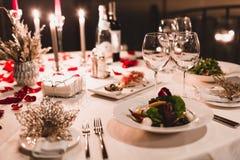 浪漫桌设置用酒,在箱子的美丽的花,空的玻璃,玫瑰花瓣和蜡烛 库存图片