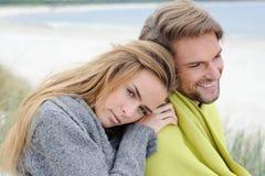 浪漫海边夫妇放松在沙丘的-秋天,海滩 免版税库存图片