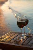 浪漫海滩场面:两杯在日落的红葡萄酒在水附近 免版税库存图片