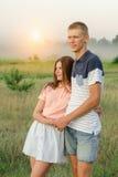 年轻浪漫爱恋的夫妇在领域中间站立 免版税图库摄影