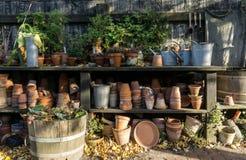 浪漫田园诗植物桌在有老减速火箭的花盆罐、工具和植物的庭院里 库存图片