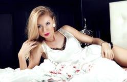 浪漫白肤金发的妇女在床上 库存图片