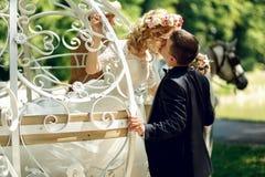 浪漫童话婚礼亲吻在ma的夫妇新娘和新郎 免版税库存照片