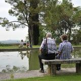 浪漫老和年轻夫妇坐公园长椅由湖 免版税库存图片