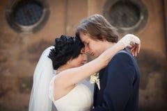 浪漫肉欲的拥抱在老教会前面的丈夫和妻子 库存图片