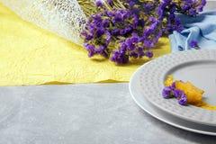 浪漫花卉构成 与紫色花花束的淡色黄色和蓝色织品  在桌背景的板材 免版税库存照片