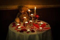 浪漫装饰桌设置了与蜡烛、玻璃、玫瑰和玩具熊 黑暗的温暖的口气 库存图片