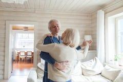 浪漫资深夫妇舞蹈华尔兹在客厅 免版税库存图片