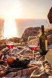 浪漫野餐有在日落的海边和山景 库存照片