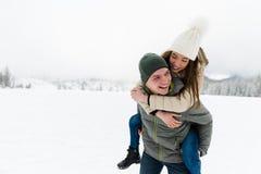 浪漫青少年的夫妇获得乐趣在雪 库存照片
