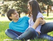 浪漫年轻夫妇一起在公园坐草和 库存照片