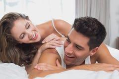浪漫年轻夫妇在床上在家 免版税图库摄影