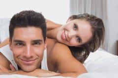 浪漫年轻夫妇在床上在家 免版税库存图片
