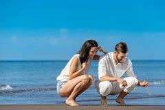 浪漫年轻夫妇得出在沙子的形状,当在蜜月时 免版税库存图片