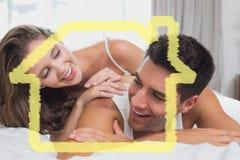 浪漫年轻夫妇的综合图象在床上在家 免版税库存照片