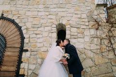 浪漫enloved新婚佳偶夫妇在老城堡墙壁附近分享一个温暖的亲吻,结合在一起使逗人喜爱的新娘花束 库存图片