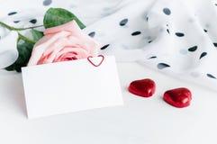 浪漫St情人节背景 罗斯、空白的爱卡片和两个心形的糖果 免版税库存照片