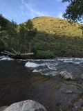 浪端的白色泡沫河和山 免版税库存照片