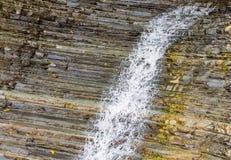 浪端的白色泡沫沿有肋骨湿山的小河瀑布 免版税图库摄影