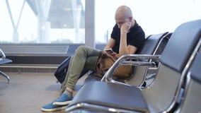 坐在休息室,飞行的不快乐的男性乘客被取消或被延迟 浪费时间的年轻人在终端 股票视频