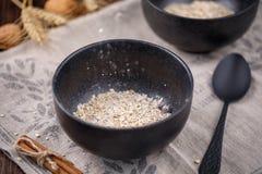 浮动在一碗干麦片燕麦粥 在木背景的静物画 免版税图库摄影
