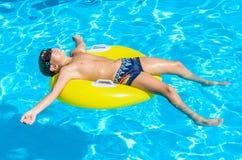 浮动在池的一个可膨胀的圈子的男孩。 库存图片