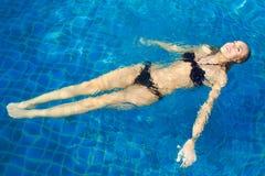 浮动在池的愉快的妇女 免版税图库摄影