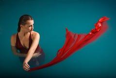 浮动在游泳池的新性感的妇女 免版税库存照片