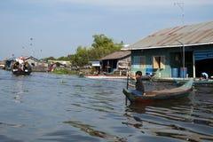 浮动村庄,独木舟的男孩驾驶河交通的 库存图片