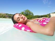 浮动池妇女的闭合的眼睛 库存图片