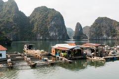 浮动渔村和岩石海岛,下龙湾,越南,亚洲东南部 E 破烂物对Ha的小船巡航 库存图片