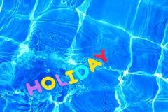 浮动的节假日池游泳字 库存图片