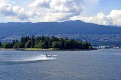 浮游物平面开始 温哥华 史丹利公园、山、天空和云彩 库存照片