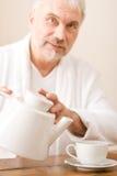 浴巾成熟咖啡的人倾吐高级穿戴 免版税库存图片