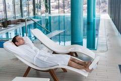 浴巾松弛近的室内游泳池的人在豪华温泉 免版税库存图片
