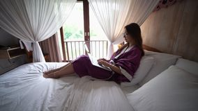浴巾的可爱的年轻女人在互联网上聊天 股票录像