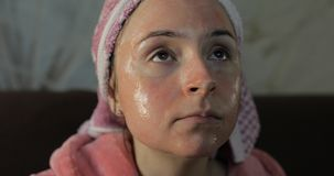 浴巾的妇女有面膜的 观看在电视的一深夜电影 库存照片