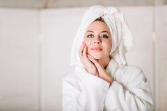 浴巾的年轻微笑的妇女有在头的毛巾的 图库摄影