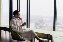 浴巾饮用的咖啡的人在窗口附近的豪华摩天大楼旅馆有全景 在a的商人 免版税库存照片