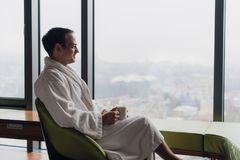 浴巾饮用的咖啡的人,看都市风景 库存图片