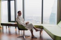 浴巾饮用的咖啡的人,看都市风景 免版税库存图片