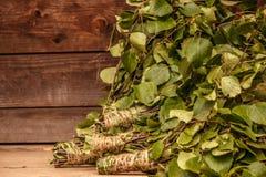 浴桦树和橡木分支的新的笤帚在黑褐色木背景 免版税库存图片