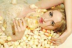浴的肉欲的妇女与黄色瓣 库存图片