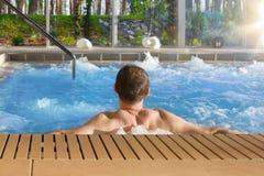 浴盆温泉的英俊的人在有大玻璃wi的豪华旅馆里 免版税库存图片